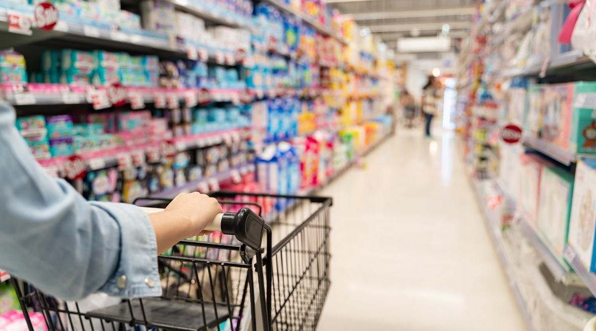 Asda - customer shopping in a supermarket concept.Shopping in supermarket a shopping cart view with motion blur.Close up of a woman shopping in a supermarket.Customer pushing a shopping cart in a supermarket.